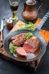 Traditional barbecue aged saddle of venison with herbs game sauce as closeup in a wrought iron skillet