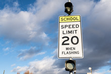 Speed Limit 20 When Flashing Sign Near School. Cloudy Sky In The Background.
