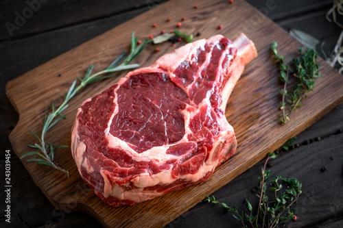 Fotografie, Obraz  raw rib eye steak premium beef on bone on wooden chopping Board