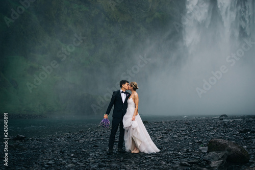 Tablou Canvas Young happy wedding couple kissing on background of waterfall, outdoors
