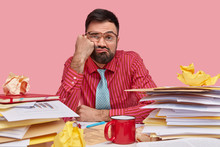 Lazy Displeased Fatigue Male Worker Keeps Fist On Cheek, Has Sleepy Look, Dressed In Formal Shirt And Tie, Works With Papers, Has Mess On Workpace, Poses Over Pink Background, Being Overload