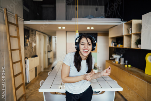 Fotografie, Obraz  Cheerful woman listening to music with large headphones and singing