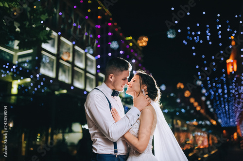 Happy and lovers newlyweds hugging against the background of the night city and light bulbs with bokeh, on the boulevard. Portrait of a stylish groom and beautiful bride with a long dress.