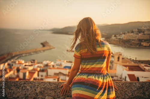 Little girl on the top of Peniscola, admiring amazing summer sunset, travel with children, wearing colorful dress, back view