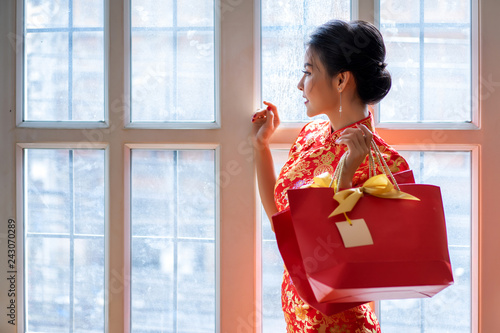 cc5ab2e61 Happy chinese woman wearing a qipao dress traditional or cheongsam hand  holding gift bags near window