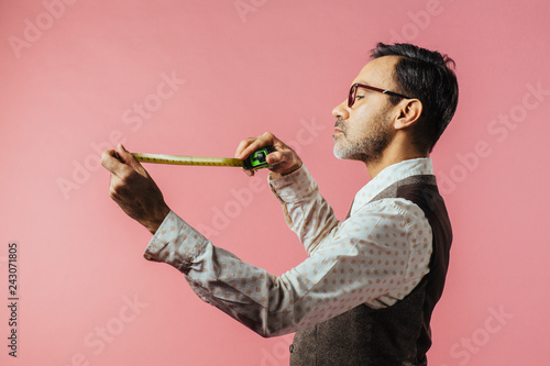 Fototapeta  Portrait of a tailor looking down at fabric measure, isolated on pink studio bac