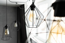 Loft Style Iron Lampshade With A Light Bulb In The Interior Living Room In Modern Apartment. Vintage Style Light Bulbs. Glass Round Bulbs With A Spiral On Wall.