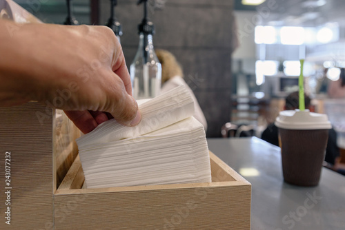 Closeup of passenger's hand taking napkin in airport cafe