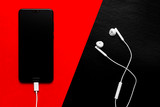 Smartphone with blank screen and earphones on red and black background top view. Headphones and device on colored background. Smartphone with earphones on color background