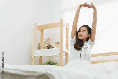 Fotografie, Obraz  Asian woman wake up in the morning, sitting on white bed and stretching, feeling