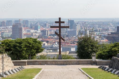 Foto  Christian cross in Slavin on background skyline of Bratislava