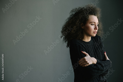 Fotografie, Tablou  Close up of teenager with depression and bulimia standing alone in grey room