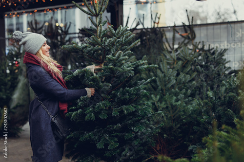 Pretty blonde girl looking for perfect Christmas tree to buy on the tree shop, outdoor Canvas Print