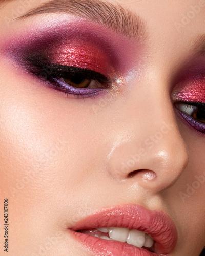 Obraz Closeup portrait of young beautiful woman with bright pink smokey eyes and lips. Fashion makeup. Studio shot. Modern summer make up. Extreme closeup, partial face view - fototapety do salonu
