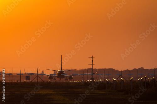 Zdjęcie XXL Samolot na szlakowym narządzaniu zdejmował przy zmierzchem z czerwonym niebem w tle