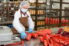 Workwoman Hanging Up Sausages ...