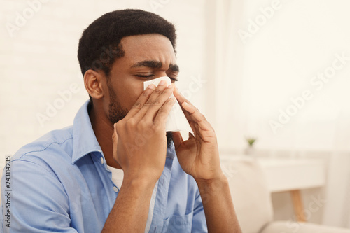 Fényképezés  African-american man man has runny nose at home