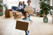 Cute Happy Mixed Race Children Enjoying Moving Day Running Carrying Holding Boxes, Excited African American Kids Laughing Playing In New Home Having Fun Unpacking, Black Family Relocation Concept