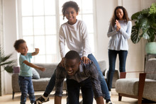 Happy African American Dad Riding Mixed Race Daughter On Back, Playful Black Family Enjoying Playing Funny Game With Kids Together In Living Room, Parents And Children Laughing Having Fun At Home