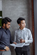 canvas print picture Mix raced couple of male business partners analyzing reports against grey wall. Indian and Chinese men in formal shirts standing in grey office boardroom. Marketing concept