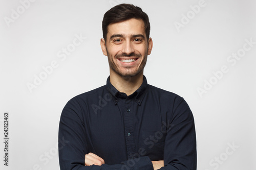 Obraz na płótnie Handsome smiling business man in blue shirt isolated on gray background