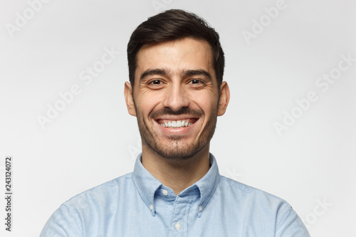 Fotografie, Obraz  Close-up portrait of handsome business man laughing, isolated on gray background