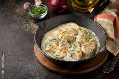 Fototapeta Chicken fillet or Turkey breast in creamy sauce with dill and garlic, in cast iron black pan on dark background. Delicious homemade food obraz