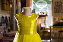 Yellow Children's Dress With Sparkles On Mannequin. Little Yellow Dress In Studio. Sewing Women's Handmade Children's Clothing. Yellow Baby Clothes