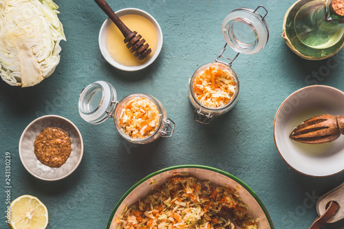 Fotografie, Obraz  Preparation of carrot cabbage salad in jars for healthy lunch is on kitchen table background, top view, with copy space