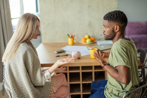 Photo  Caucasian blonde woman has some misunderstanding with her african hipster boyfriend, who is having surprised and puzzled look, couple is sitting in cozy living room with modern interior