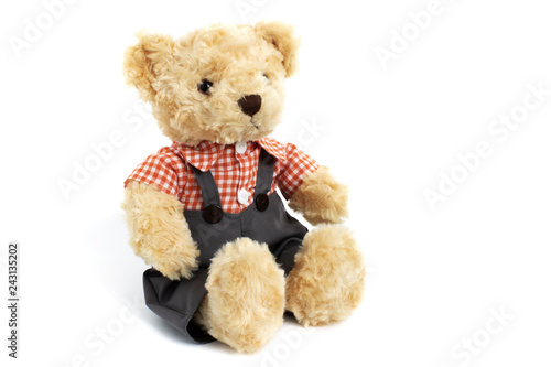 Dressed toy teddy bear in shirt and trousers is sitting on white background