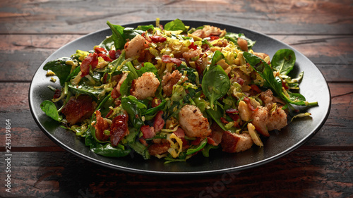 Fototapeta Roasted brussel sprouts, bacon warm salad with spinach, croutons and hazelnuts obraz