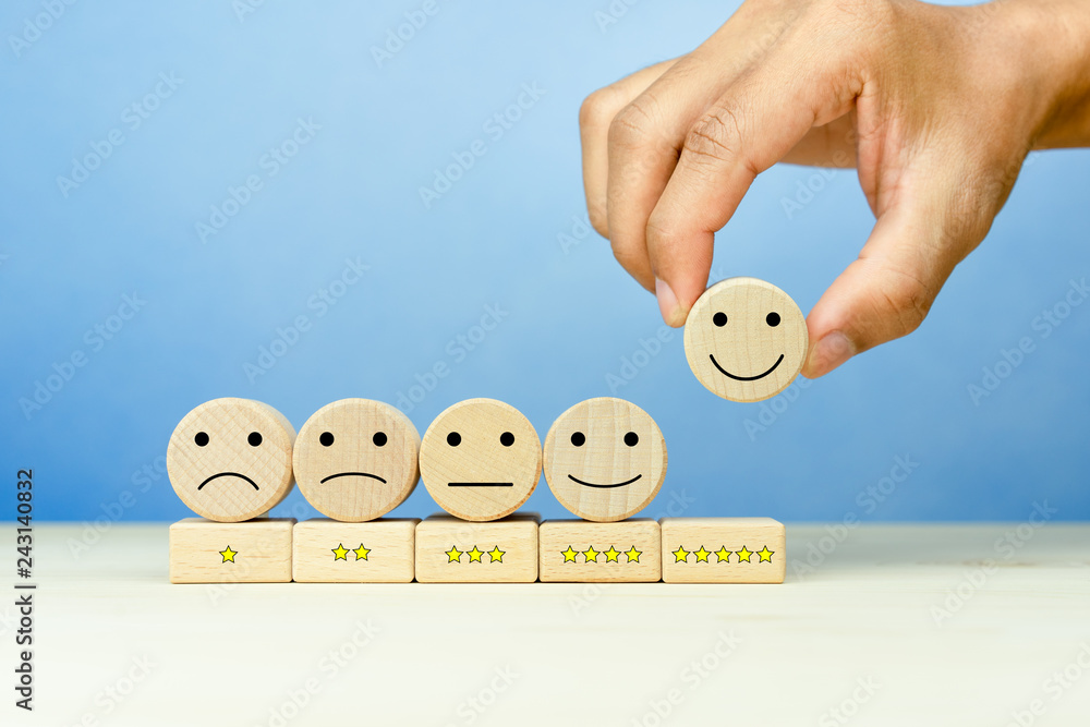 Fototapeta Customer service evaluation and satisfaction survey concepts. The client's hand picked the happy face smile face icon and five star symbol on wooden cube on table
