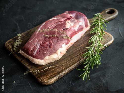 Raw uncooked duck breast with rosemary and thyme on wooden cutting board. - 243141277