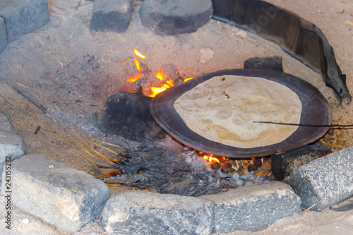Traditional arabic pita bread cooking on fire in bedouin dwelling Wallpaper Mural