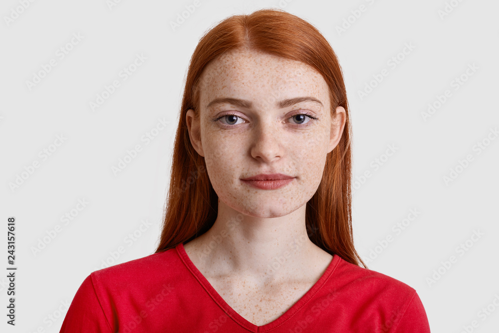 Fototapeta Headshot of attractive red haired European woman with freckled skin, looks seriously at camera, has minimal make up, wears red sweater, isolated over white background. Natural beauty concept