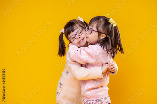 Valokuva Charming positive sisters with chromosome abnormality hugging each other