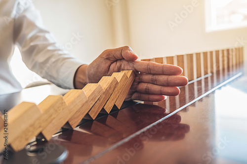 Cuadros en Lienzo Problem Solving,Close up view on hand of business woman stopping falling blocks on table for concept about taking responsibility