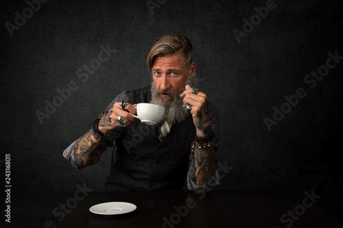 Fotografía  Porträt eines bärtigen Mannes mit einem Tasse Kaffee, vor dunklem Hintergrund