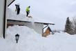 canvas print picture - Zwei Männer schaufeln hohen, schweren Schnee von einem Hausdach