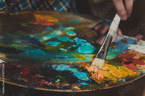 creativity, hand of a man with a brush on the canvas Canvas Print