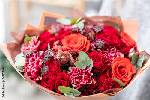 beautiful fresh cut bouquet of mixed flowers in woman hand. the work of the florist at a flower shop. Bright juicy red colors © malkovkosta
