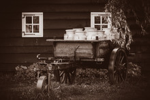 Old Traditional Dutch Cans In A Carriage In Village. Holland, Netherlands . Image In Sepia Color Style