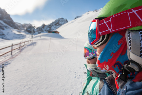 Portrait of child and mom skiing in the mountains.