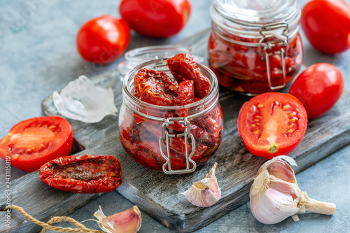 Sun dried tomatoes with herbs and olive oil in jar.
