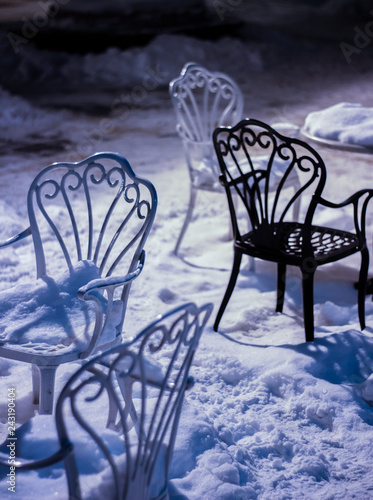 Photo  Cafe tables covered with snow illuminated by street lights