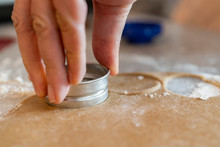 Close Up Of A Rolling Pin And Hands Who Are Cutting Out Cookies Of The Biscuit Dough