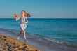 Red-haired girl, playing with a toy airplane, runs along the beach of the sea against the blue summer sky and enjoys the rays of the sun and freedom..