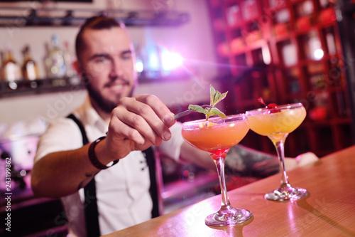 Fotografía  handsome bartender prepares an orange alcoholic cocktail and smiles on the backg