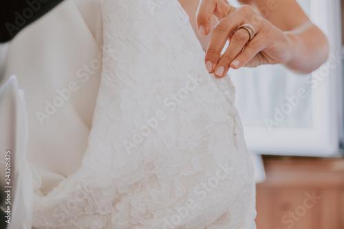 Bride's hands unbuttoning wedding dress